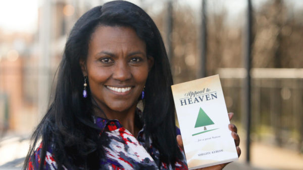 """Shegitu Kebede holds her newest book """"Appeal to Heaven"""" on Nov. 11, 2016, in downtown Fargo. Michael Vosburg / Forum Photo Editor"""