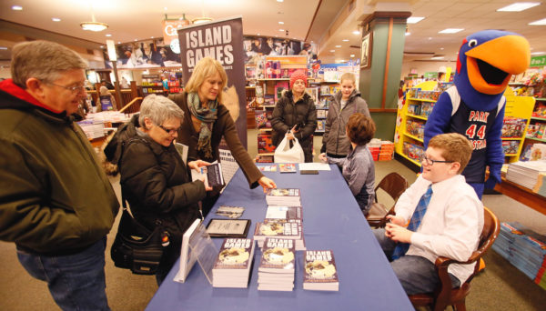 """Caleb Boyer meets customers as they look over his book titled """"Island Games"""" during a signing session at Barnes and Noble on Saturday, Dec. 17, 2016. David Samson / The Forum"""